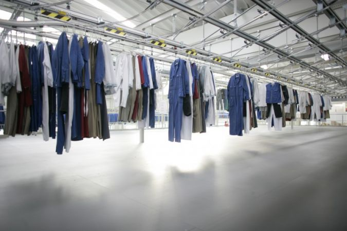 A modern conveying and sorting system arranges the loading of a washing machine according to customer and wearer