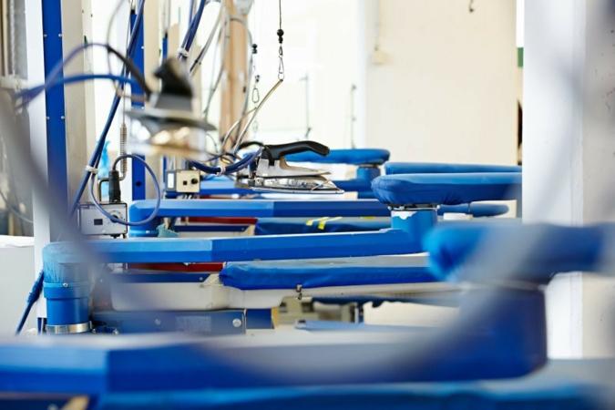 Auf Industrie-Bügelanlagen erhält die Kleidung das perfekte Finish. Photo: Packservice